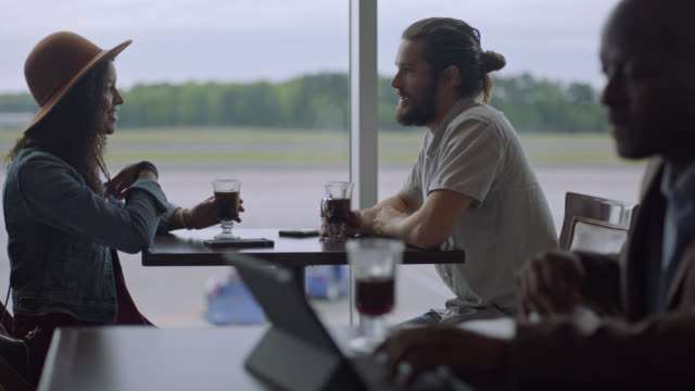 young diverse millennial couple chat while they wait by window in airport terminal cafe. - aspettare video stock e b–roll