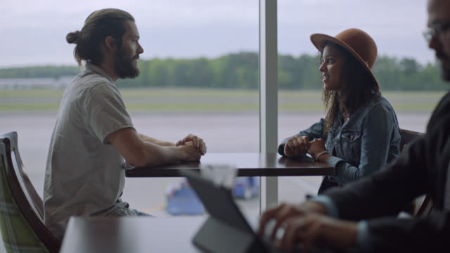 young diverse millennial couple sits down by window at airport terminal cafe. - black and white video stock e b–roll