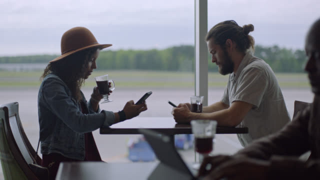 young diverse millennial couple with coffee use smartphones while they wait by window in airport terminal cafe. - aspettare video stock e b–roll