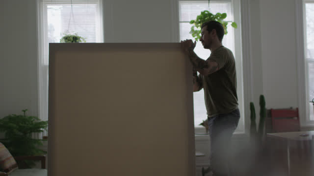 WS SLO MO. Young DIY artist inspects large blank canvas after assembling it in modern apartment.