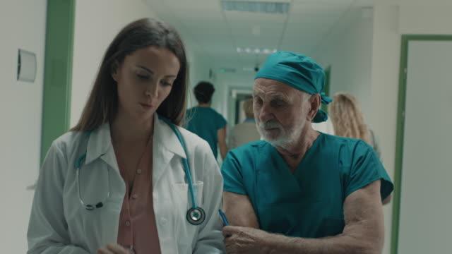 vídeos de stock, filmes e b-roll de doutor novo e cirurgião sênior que andam e que falam - respect