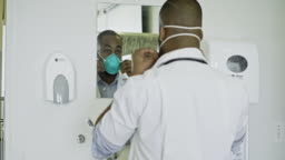 Young doctor getting ready with surgical mask in hospital