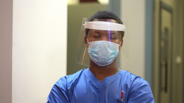 young doctor in hospital wearing protective workwear - only young men stock videos & royalty-free footage