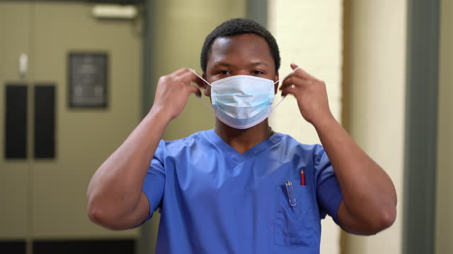 young doctor in scrubs taking off mask - only young men stock videos & royalty-free footage
