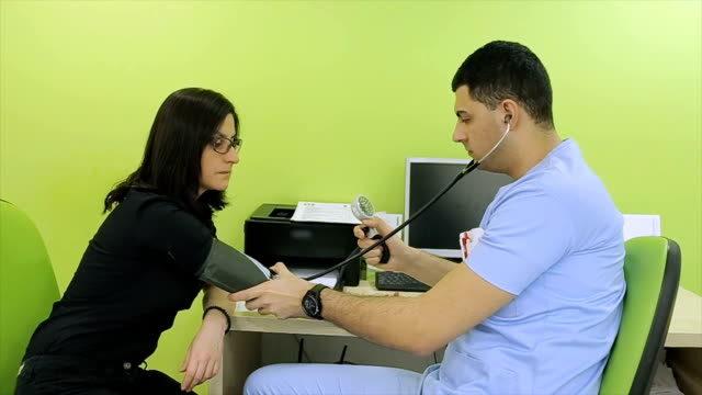 Young doctor measures the blood pressure of the patient