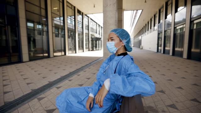 vídeos y material grabado en eventos de stock de young doctor takes break on bench near hospital wearing surgical mask, gown and cap - neumonía