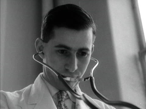 A young doctor uses a stethoscope 1958