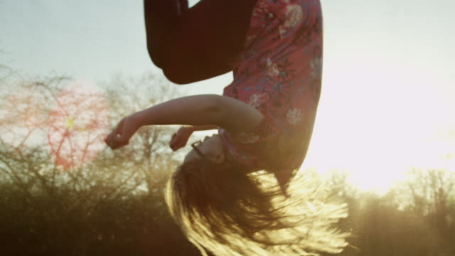 stockvideo's en b-roll-footage met young down syndrome woman on trampoline at sunset - trampoline