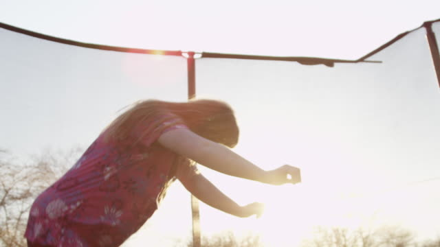 Young Down syndrome woman on trampoline at sunset