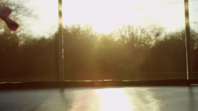 vídeos de stock e filmes b-roll de young down syndrome woman on trampoline - trampolim equipamento desportivo