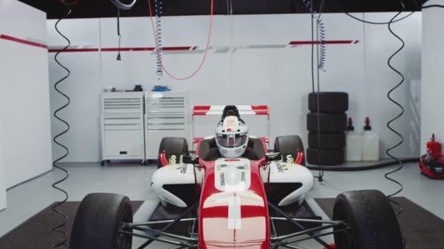 young driver sitting in racecar at pit stop - casco da motociclista video stock e b–roll