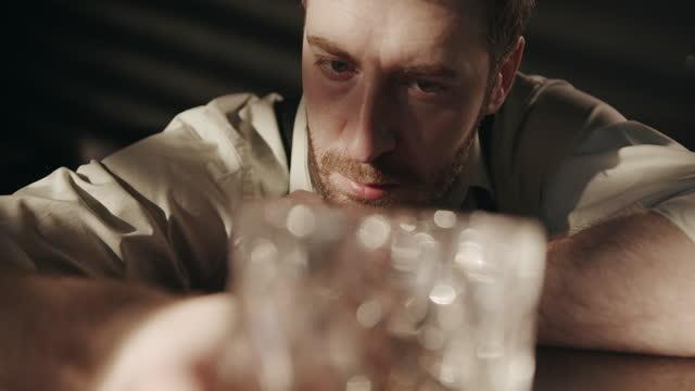 シャツとネクタイを着た若い酔っ払った悲しいホワイトカラーの労働者は、思慮深くウイスキーでガラスを見ています - white collar worker点の映像素材/bロール