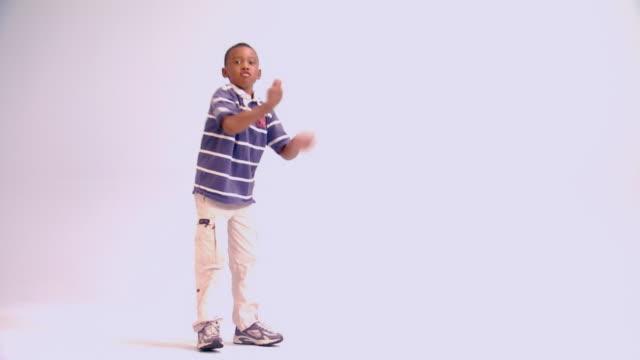vídeos y material grabado en eventos de stock de young elementary age boy dancing - expresión facial