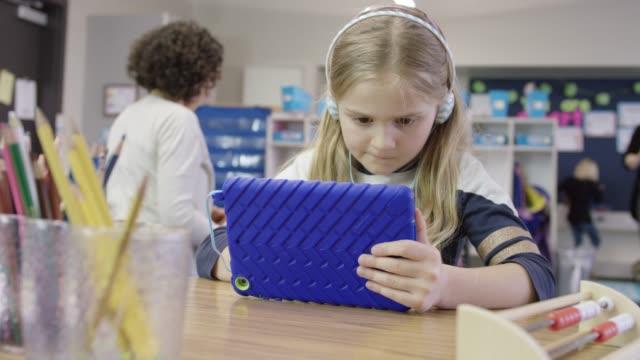 vídeos de stock e filmes b-roll de young elementary age girl using tablet in school - escola primária