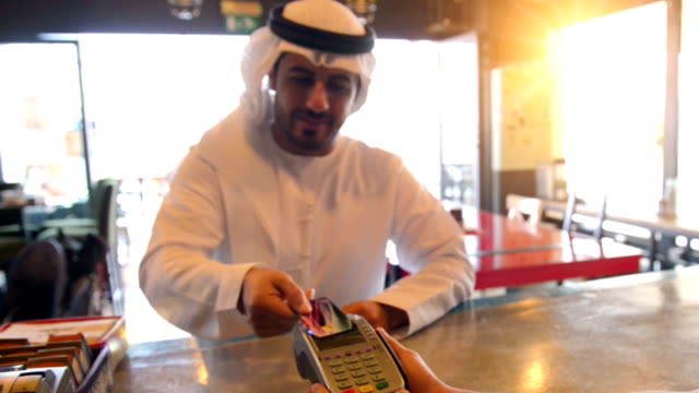 Young Emirati man paying with contactless credit card