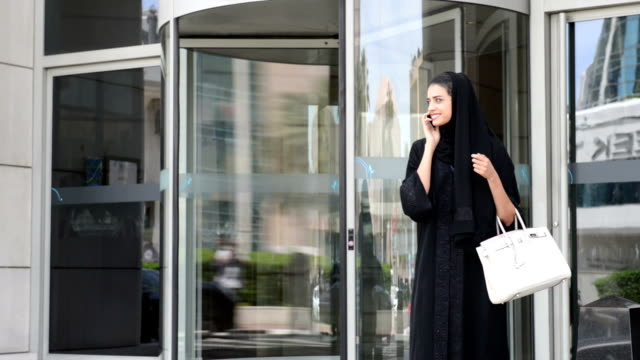 young emirati woman by the revolving door - entrance sign stock videos & royalty-free footage