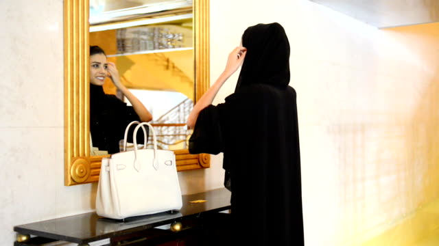 young emirati woman by the wall mirror - hijab stock videos and b-roll footage