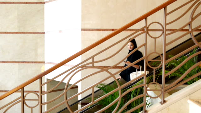 young emirati woman on the escalator - escalator stock videos & royalty-free footage
