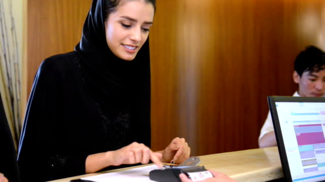 Young Emirati woman paying via credit card
