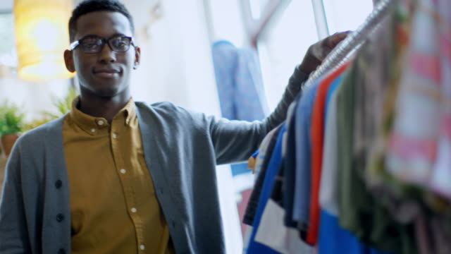 young employee at local clothing store smiles at camera - african american culture stock videos & royalty-free footage