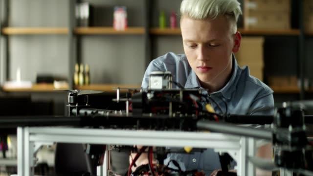 若いエンジニアがはんだ付けおよびデバイスのプロトタイプを改善 - プロトタイプ点の映像素材/bロール