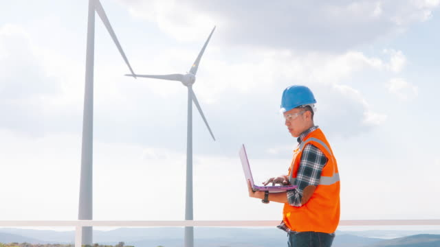 Young engineer man looking and checking wind turbines at field