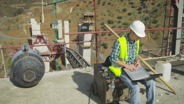 HA young engineer sitting in construction site, working on laptop computer, at end of clip looking to camera