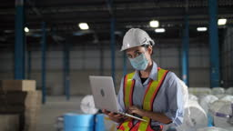 Young engineer using a laptop in an industrial place of work Look at camera