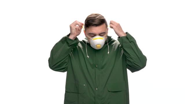 若いエンジニア、労働者は白い背景、スローモーションに保護マスクと安全装置を置きます - レスピレーターマスク点の映像素材/bロール