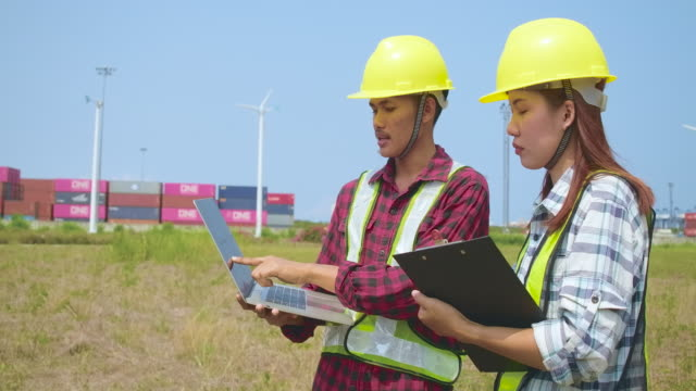 young engineers and workers having a meeting at wind farm - headwear stock videos & royalty-free footage