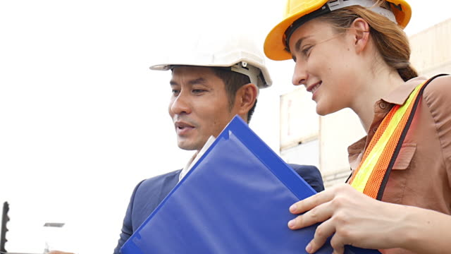 giovani ingegneri in piedi nel cantiere navale che tracciano l'inventario del carico e controllano la scatola del contenitore per la sicurezza. - elmetto da cantiere video stock e b–roll