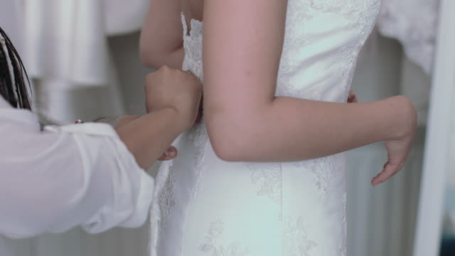vídeos de stock, filmes e b-roll de young entrepreneur helping bride with dress fitting - vestido de noiva