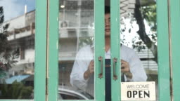 Young entrepreneur man open the door in the morning at his coffee cafe shop.