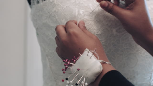Young entrepreneur pinning wedding dress on dummy