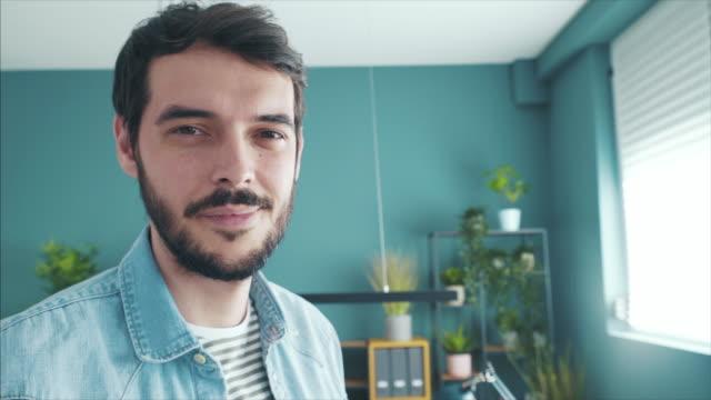 vidéos et rushes de portrait de jeune entrepreneur dans le bureau. - regarder fixement