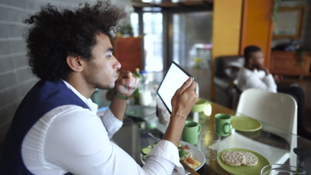 Young entrepreneur using digital tablet while having breakfast