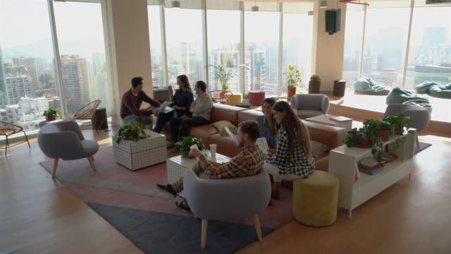 young entrepreneurs in a meeting at a coworking office using documents and laptop while another group is relaxing at background - coworking stock videos & royalty-free footage