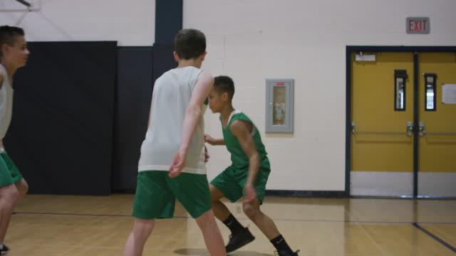 少年民族裁判所をバスケット ボールのドリブル - 体育館点の映像素材/bロール