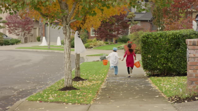 Young ethnic children running between houses trick or treating gleefully