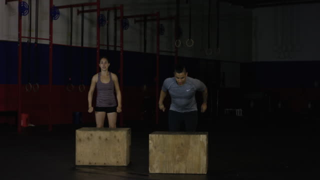 Young ethnic couple exercising in industrial gym doing box jumps