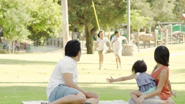 若い民族家族と 3 人の子供と一緒に屋外でリラックスした公園鬼ごっこ - 継父点の映像素材/bロール
