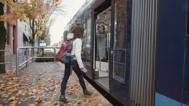 young ethnic female adult boarding a streetcar - bus stop stock videos & royalty-free footage