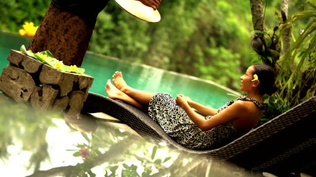 young ethnic female at balinese jungle spa resort - パレオ点の映像素材/bロール