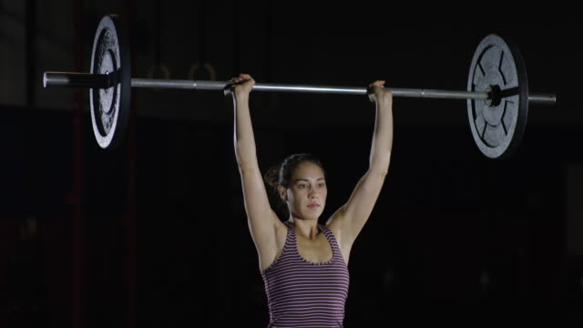 young ethnic female athlete doing push presses in a gym - weightlifting stock videos & royalty-free footage