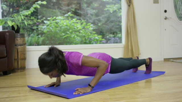 Young ethnic female exercising at home in living room