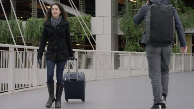 Young Ethnic Female  Pulling Her Suitcase Across the Airport Sky Bridge