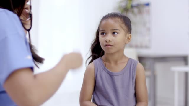 vídeos de stock, filmes e b-roll de menina étnica nova que tem o check-up médico - enfermeira pediátrica
