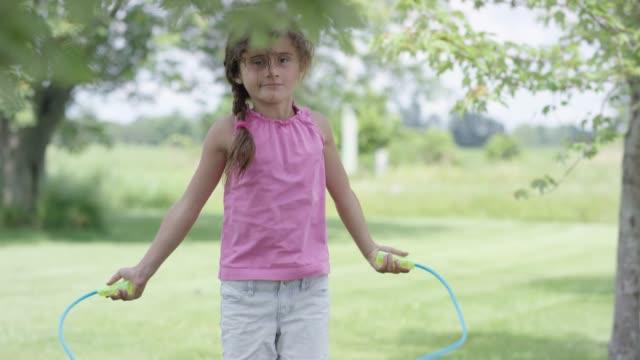 vídeos de stock e filmes b-roll de young ethnic girl jump roping outside on a sunny day - corda de saltar