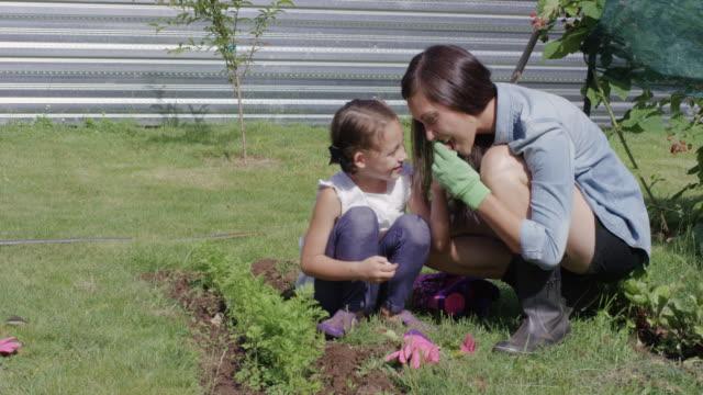 vidéos et rushes de jeune maman ethnique jardiner avec sa fille - gant de jardinage