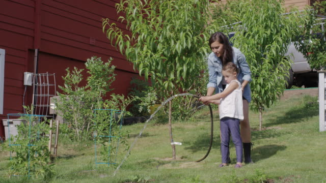 Young ethnic mother gardening with her daughter